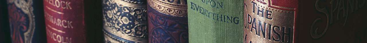 Ett hyllplan fylld med böcker med ryggen utåt
