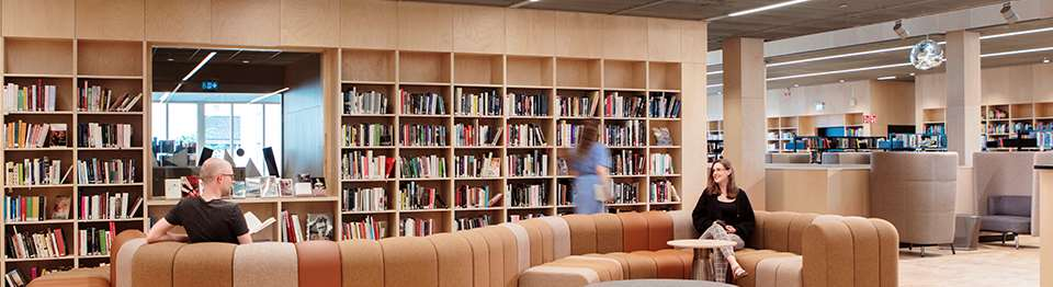 Personer sitter och läser böcker på stadsbiblioteket.